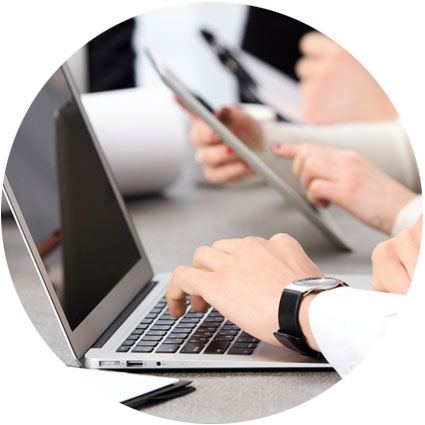 Business professional typing on a silver laptop