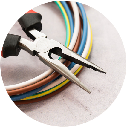A pair of pliers resting on reels of multi coloured cable