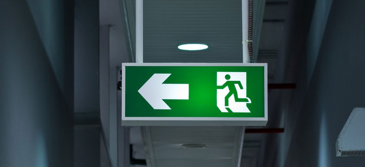 Emergency exit sign illuminated in a dark hall way
